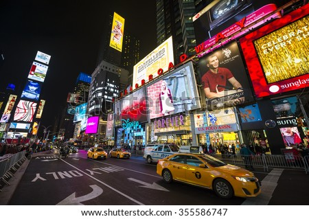 NEW YORK CITY, USA - DECEMBER 22, 2015: Yellow New York taxi passes crowds gathering under the bright lights of Times Square in the build-up to New Year's Eve.