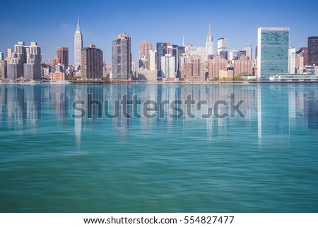 New York City view of Manhattan and The East River with reflections of NYC buildings.