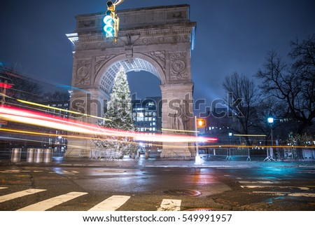 NEW YORK - JAN 3, 2017: beautiful long exposure of car streaks past Washington Square North Christmas tree under arch at night in NYC. Greenwich Village is a famous neighborhood in Lower Manhattan.