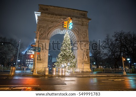 NEW YORK - JAN 3, 2017: green light over crosswalk at Washington Square North with Christmas tree under famous arch monument at night in NYC. During the holidays, WSP has an annual tree.