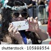 NEW YORK - JUNE 23: Actress Annabella Sciorra as Queen Mermaid takes pictures with iPhone at 30th annual Mermaid parade on Coney Island in Brooklyn on June 23, 2012 in New York City. - stock photo