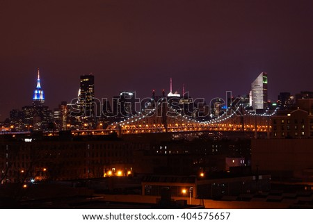 NEW YORK, UNITED STATES -DECEMBER 01, 2013: Quennsboro bridge in the night from Queens. Empire State can be seen in the background.