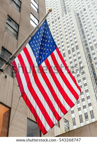 NEW YORK, USA - May 01, 2016: American flag on the Rockefeller Center background in New York City, Midtown Manhattan