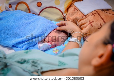 Newborn and Mother in hospital after giving birth (focused on newborn)