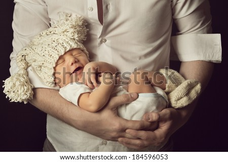 newborn baby boy smiling in woolen hat, new born sleeping on father hand, small kid happy laughing