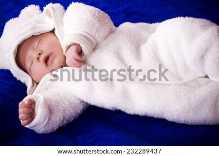 Newborn baby child wearing a white sleeper.