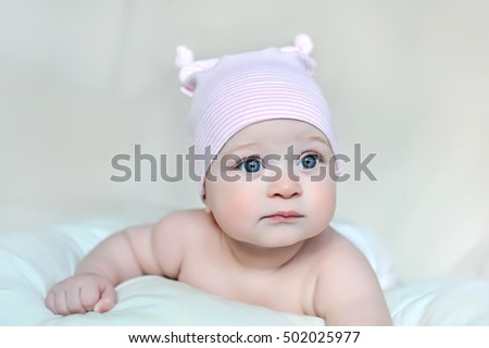 newborn baby girl in pink hat and mittens on a white bed