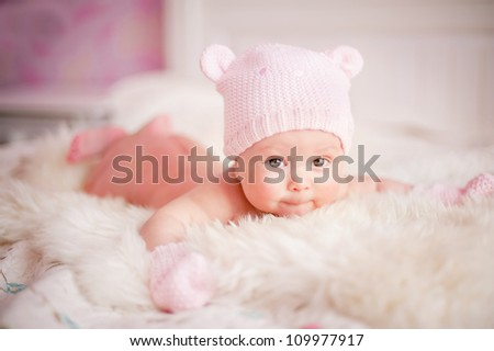 newborn baby girl in pink knitted bear hat lies at fur