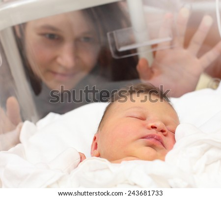 Newborn baby girl sleeping in a incubator. Her mother looking at. Close up with shallow DOF.