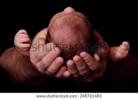 Newborn baby in the arms of his father, close-up, black background