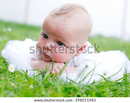 Newborn baby laying on the grass