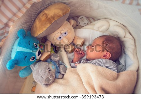 newborn boy lying with his toys in a cradle