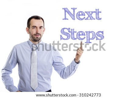 Next Steps - Young businessman with small beard pointing up in blue shirt