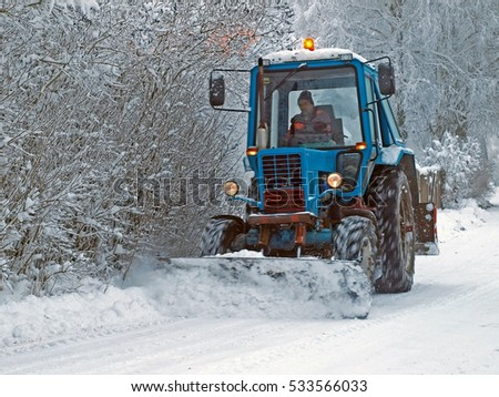 NICA, LATVIA - DECEMBER 8, 2012: Tractor is removing snow from the country road with shovel blade.