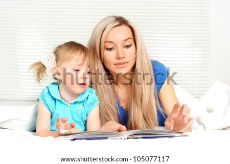 Nice caucasian mother and daughter lying on the bed with a book
