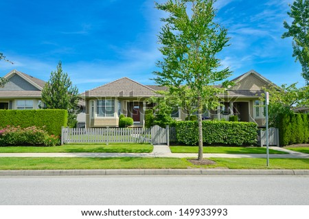 Nice looking house behind the green and wooden fence at the empty street in the suburbs of Vancouver, Canada.