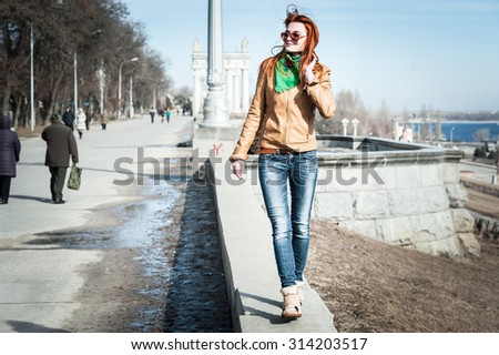 Nice red-haired girl in sunglasses walking outdoors.