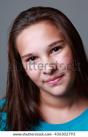 Nice studio shots of a a 12 year old girl making faces on a grey background