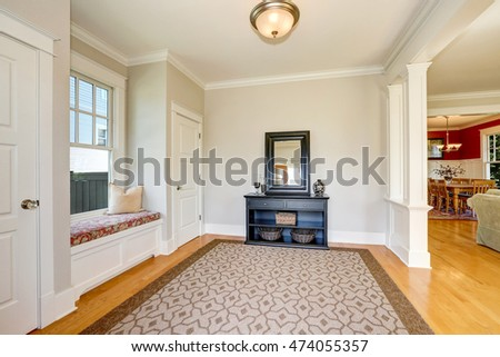 Nicely decorated hallway interior with soft beige walls, Black cabinet with mirror and wicker baskets and comfortable window seat between two closets. Northwest, USA