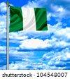 Nigeria waving flag against blue sky - stock photo