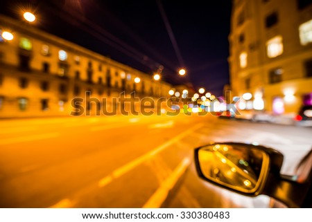 Night city lights reflected in the mirror of the car, the car goes on the road. Wide-angle view and defocused image, from the car window