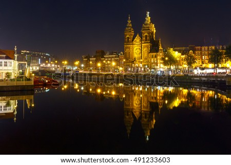 Night city view of Amsterdam canal with Basilica of Saint Nicholas and its mirror reflection in the water, Holland, Netherlands. Long exposure.