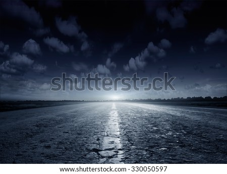 Night road against the background of cumulus clouds