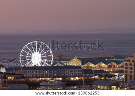 Night shot towards Cape Town waterfront showing big wheel and sea horizon