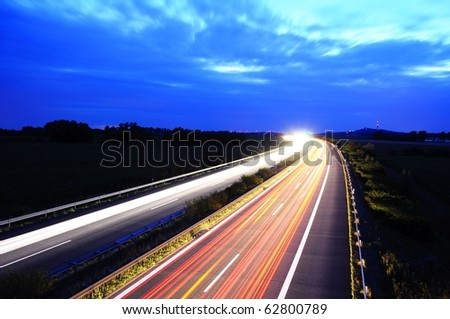 night traffic on busy highway with cars lights and blue sky