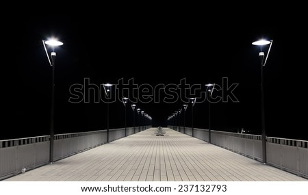 Night view of a wooden pier and lamp posts.