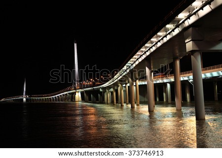 Night View of Cross Shenzhen and Hongkong highway bridge with all illumination lights, road lamps, traffic lights on over Shenzhen Bay