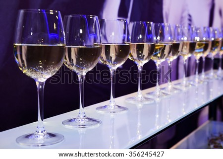 Nightclub wine glasses with white wine lit by party festive lights on dark-purple background, nightlife entertainment industry