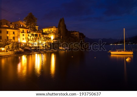 Nightfall overlooking part of the town Varenna on lake Como. Buildings and a sailboat are illuminated by multiple lights reflecting on the water
