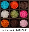 Nine colorful balls of yarn in a printers box, in autumn colors - stock photo