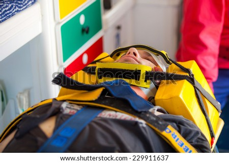 NINE, PORTUGAL - APRIL 12, 2014: Injured man and an emergency worker inside an ambulance at a scene of a train accident simulation in Nine train station