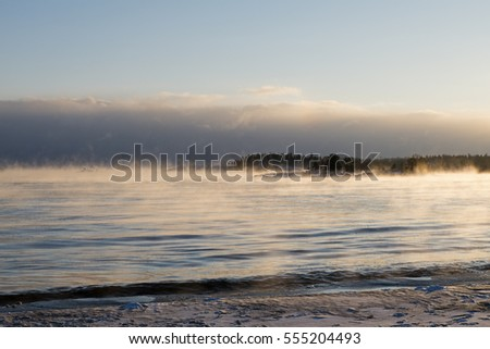 "Non-freezing abnormally warm ""boiling"" water in extremely cold on winter sunset, January, Lake Ladoga, Karelia, Russia. It is the largest freshwater lake by area in Europe."