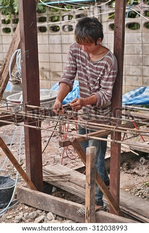 Nong Khai, Thailand - September 1, 2015: Worker fasten the steel rods with wire to make steel frame for rebuild home at Nong Khai, Thailand