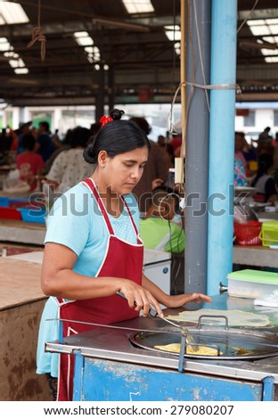 Nongkhai, Thailand - May 09: Unidentified Indian's women made Roti (KIND OF INDIAN FOOD MADE OF FLOUR) for her customer at RATTANAWAPEE market on Phonphisia in Nongkhai, Thailand on May 09, 2015.
