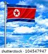 North Korea waving flag against blue sky - stock photo