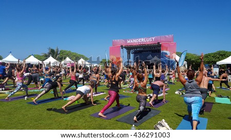 NORTH SHORE, HAWAII - FEBRUARY 28: People raise arms over head in warrior one during outdoor yoga class facing stage at Wanderlust yoga event on the North Shore, Hawaii on February 28, 2016.