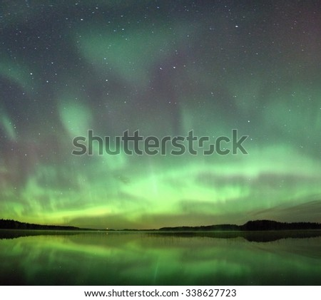 Northern lights (Aurora Borealis) in the night sky over a beautiful lake in Finland. Vibrant green colors on the sky and reflections on the still water of the lake.