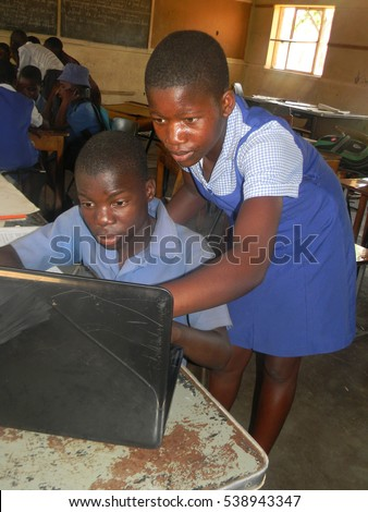 Norton Zimbabwe,November 1 2016.  Seated Primary  schoolboy  and   standing  girl  using  a  laptop  whilst  inside  a classroom  at  school.