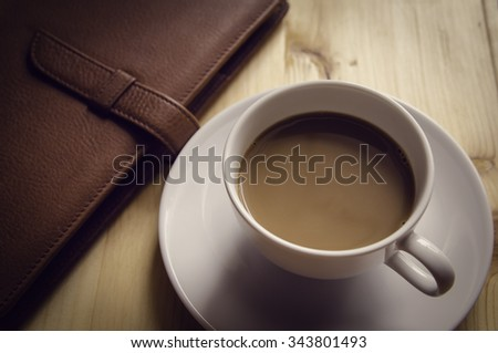 Notebook and Cup of Coffee on Wooden