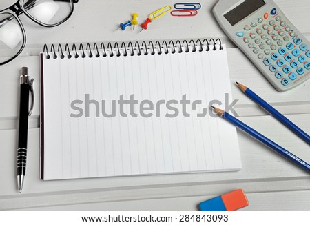 Notebook and office supply on table