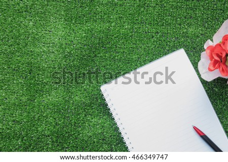 notebook and pen on artificial grass