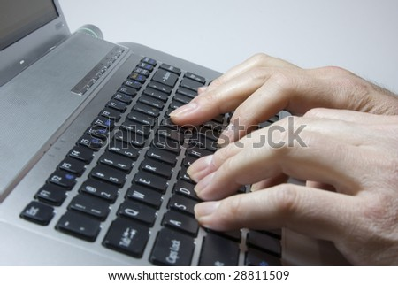 Notebook close-up photo, male hands typing on a laptop