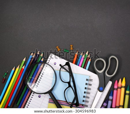 notebook, exercise book, scissors and pencils on black board background. Back to school concept