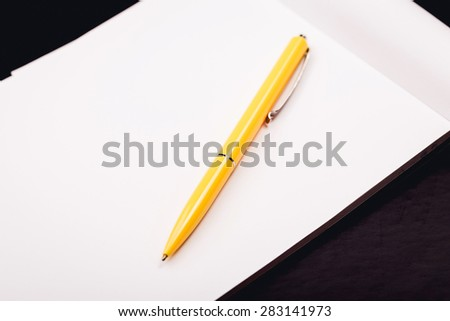 notepad with yellow pen on a black background