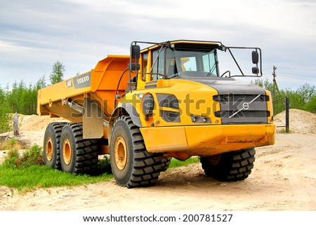 NOVYY URENGOY, RUSSIA - JUNE 24, 2014: Yellow Volvo A40F articulated dump truck at the city street.