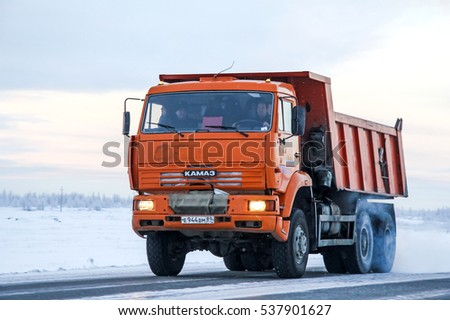 NOVYY URENGOY, RUSSIA - NOVEMBER 24, 2012: Dump truck Kamaz 6520 at the interurban road through the snow covered tundra.